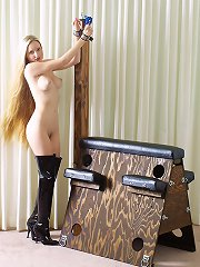 Blonde with long hair is bound to wooden bondage horse